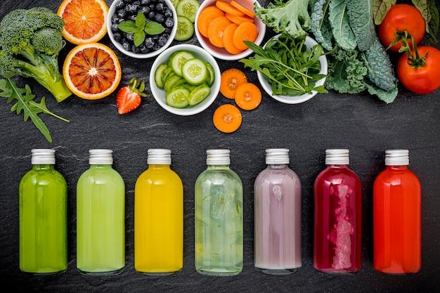 Kolorowe zdrowe koktajle i soki w butelkach ze świeżymi owocami tropikalnymi na ciemnym tle kamienia.