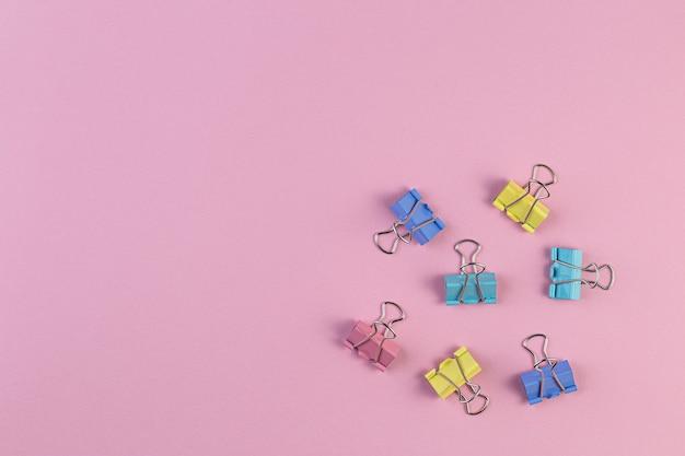Kolorowe żelazne spinacze do papieru na różowej ścianie, spinacz do segregatorów to proste urządzenie do łączenia arkuszy papieru ze sobą, metalowe spinacze w chaosie. materiały biurowe. miejsce na tekst.