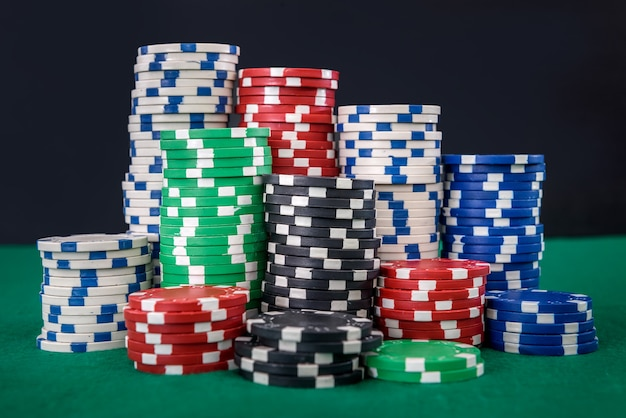 Kolorowe żetony do gry w stosach na zielonym stole z bliska