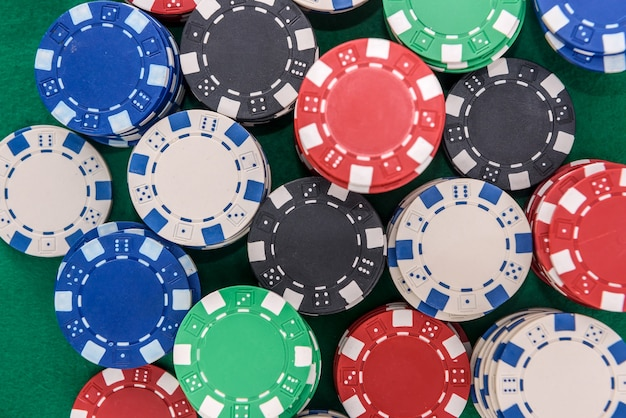 Kolorowe żetony do pokera na zielonym stole