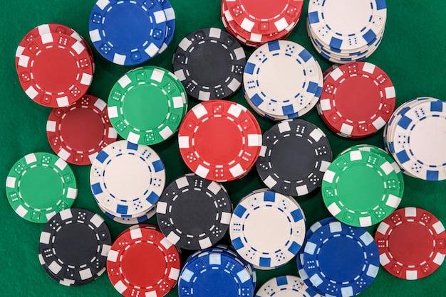 Kolorowe żetony w kasynie na zielonym filcu tabeli z bliska