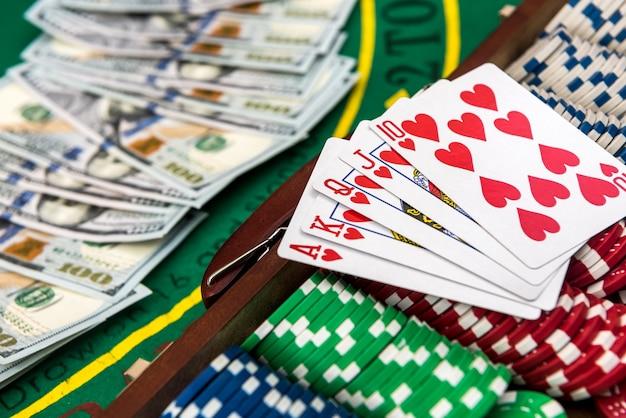 Kolorowe żetony z dolarów amerykańskich w drewnianym pudełku na zielonym stole do gry.
