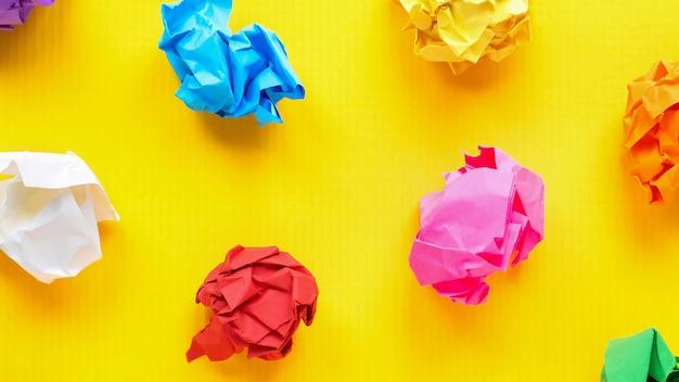 Kolorowe zgniecione papiery na żółtym tle