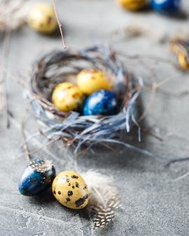 Kolorowe żółte i niebieskie pisanki przepiórcze w małych gniazdach. jaja przepiórcze na katolickie i prawosławne święta wielkanocne.
