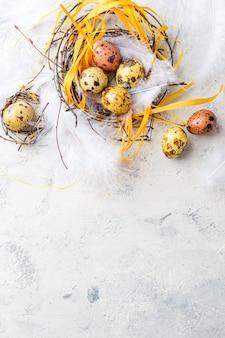 Kolorowe żółto-brązowe pisanki przepiórcze z piórami w małych gniazdkach. niewielka głębokość pola. widok z góry.