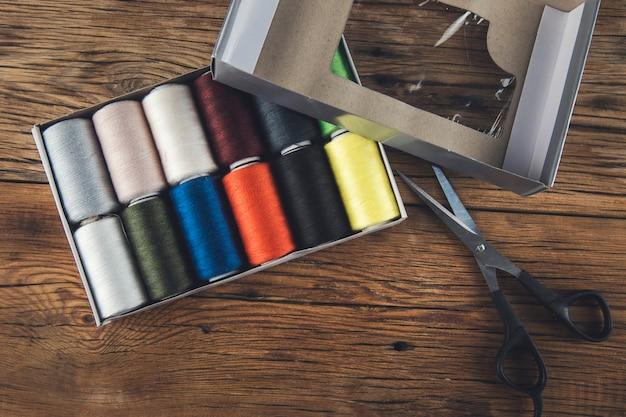 Kolorowe zwoje nici i nożyczki na stole