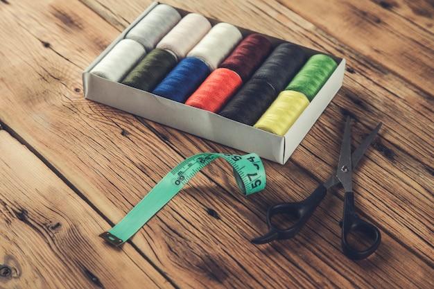Kolorowe zwoje nici z nożyczkami i miernikami na stole