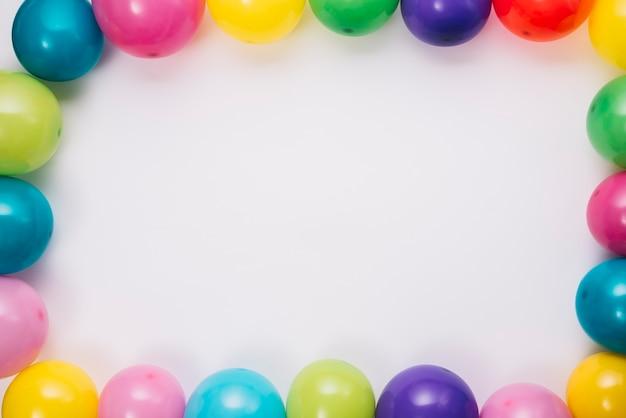 Kolorowi balony graniczą na białym tle z przestrzenią dla pisać tekscie