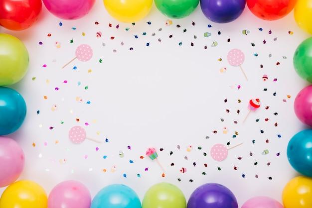 Kolorowi balony graniczą z confetti i wsparciami na białym tle