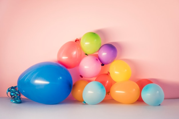 Kolorowi balony na różowym tle