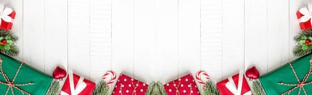 Kolorowi bożenarodzeniowi prezentów pudełka na białym drewnianym sztandaru tle graniczą projekt