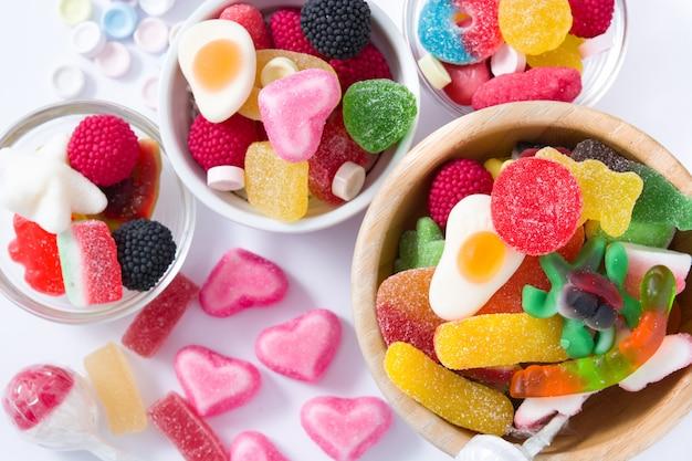 Kolorowi childs cukierki, fundy w pucharze na bielu i