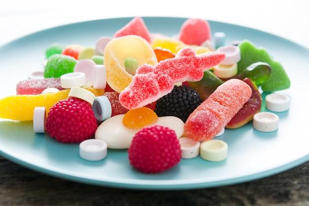 Kolorowi childs cukierki, fundy w talerzu na drewnianym stołu zakończeniu i up