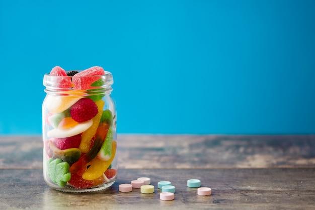 Kolorowi childs cukierki i fundy w słoju na drewnianym stole