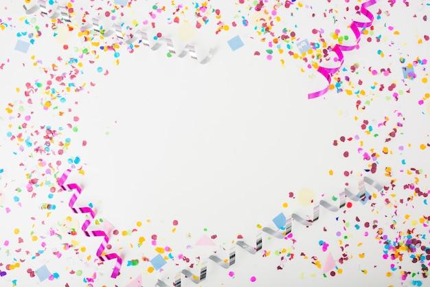Kolorowi confetti i fryzowania streamers na białym tle z przestrzenią dla teksta