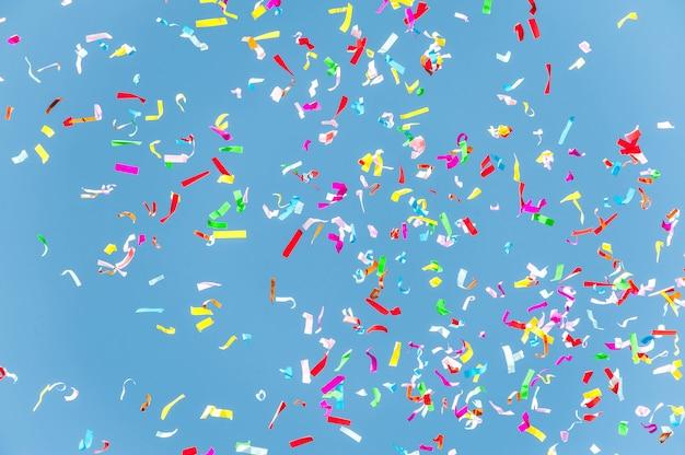 Kolorowi confetti w niebieskim niebie