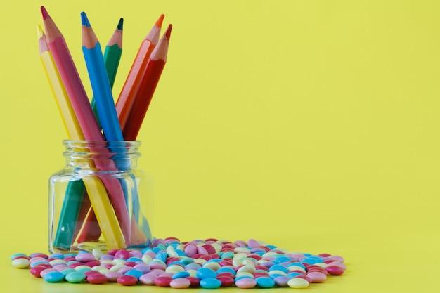 Kolorowi cukierki i słój na żółtej ścianie