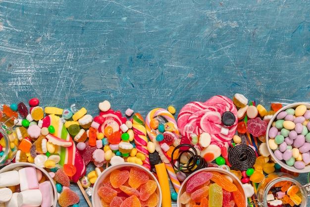 Kolorowi cukierki mieszający na błękitnym tle