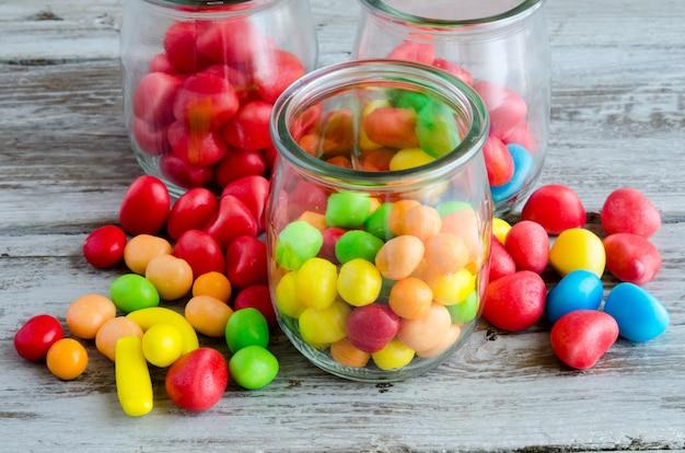 Kolorowi cukierki w szklanym słoju i rozrzuceni na stole