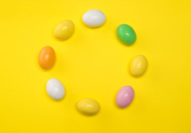 Kolorowi cukierków jajka na kolorze żółtym.