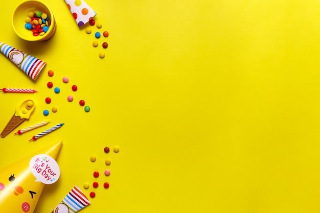 Kolorowi czekoladowi cukierki na żółtym tle