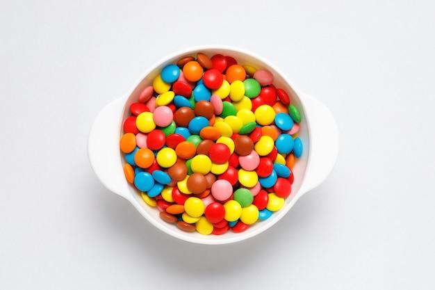 Kolorowi czekoladowi cukierki w białym pucharze