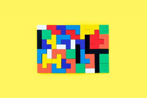 Kolorowi drewniani bloki różni kształty łamigłówki na żółtym tle. naturalne, ekologiczne zabawki. koncepcja kreatywnego, logicznego myślenia. tło z geometrycznych kształtów drewnianych klocków.