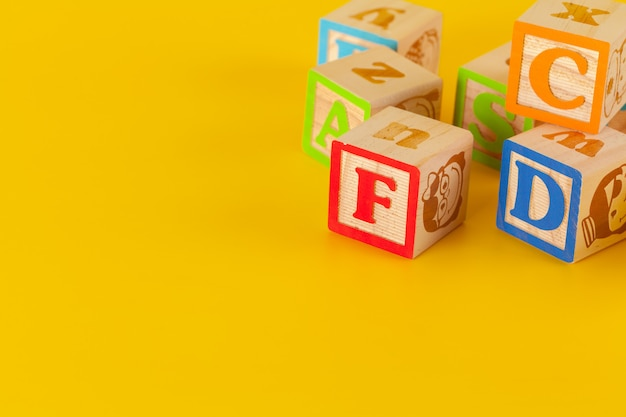 Kolorowi drewniani bloki z listami na żółtym koloru tle