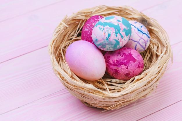 Kolorowi easter jajka w gniazdeczku na różowej drewnianej powierzchni