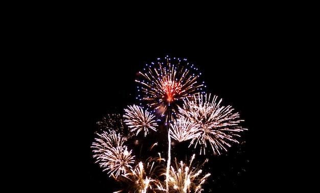Kolorowi fajerwerki na nocnym niebie z błyskotaniem