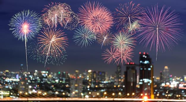 Kolorowi fajerwerki na plamy miasta linii horyzontu tle przy nocą