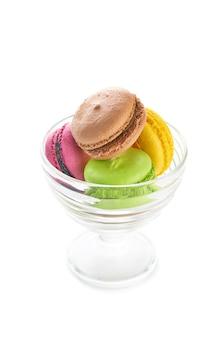 Kolorowi francuscy macaroons w szklanym pucharze na białym tle