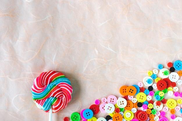 Kolorowi guziki i zawijasa lizak na różowym morwa papierze