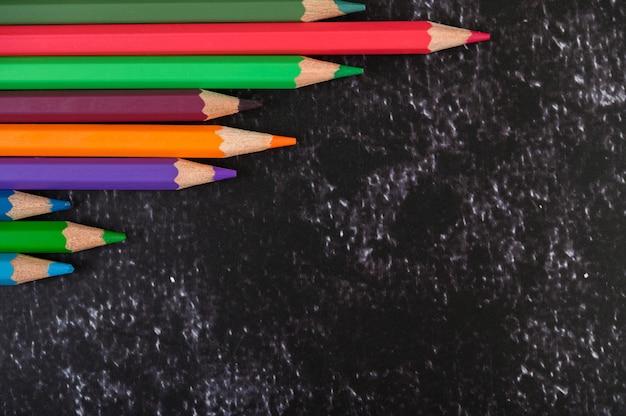 Kolorowi kredkowi ołówki z trójbokiem kształtują na biel powierzchni z kopii przestrzenią. widok z góry
