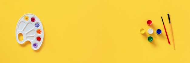 Kolorowi kwiaty na artystycznej palecie, muśnięcie, guasz na żółtym tle, kopii przestrzeń. kolory latem koncepcja kreatywnych