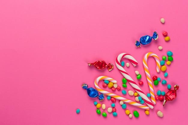 Kolorowi lizaki na różowym tle