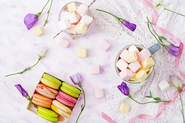 Kolorowi macaroons i marshmallows na lekkim tle. leżał płasko. widok z góry