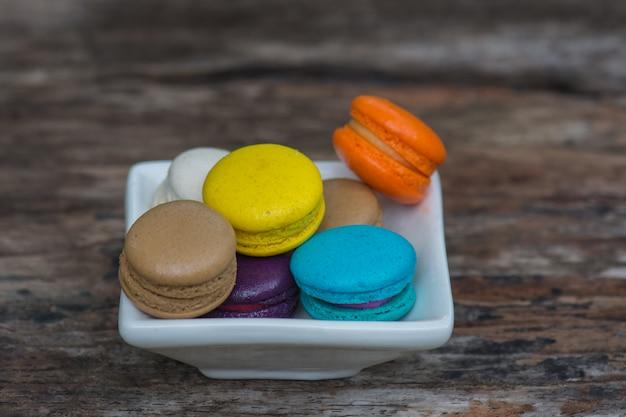 Kolorowi macaroons w naczyniu na drewnianym stole