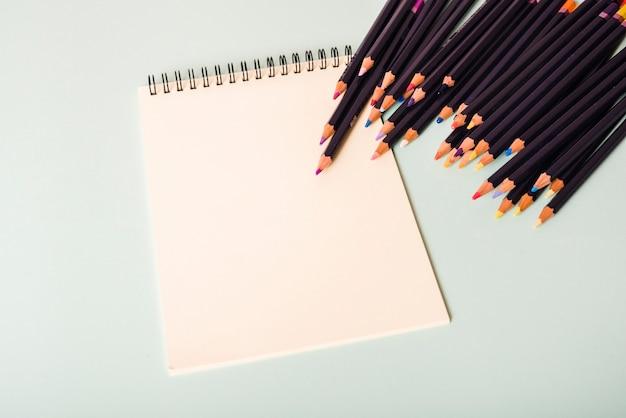 Kolorowi ołówki i pusty biel ruszać się po spirali notepad na białym tle