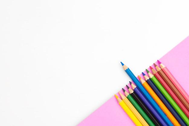 Kolorowi ołówki na zielonej części tapetują na białym tle z copyspace