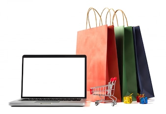 Kolorowi papierowi torba na zakupy, laptop z pustym ekranem na białym tle