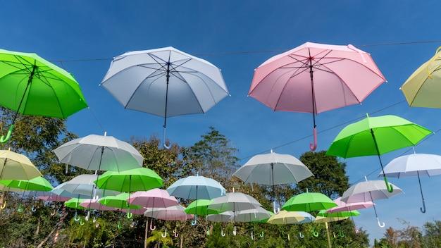 Kolorowi parasole w niebieskim niebie.