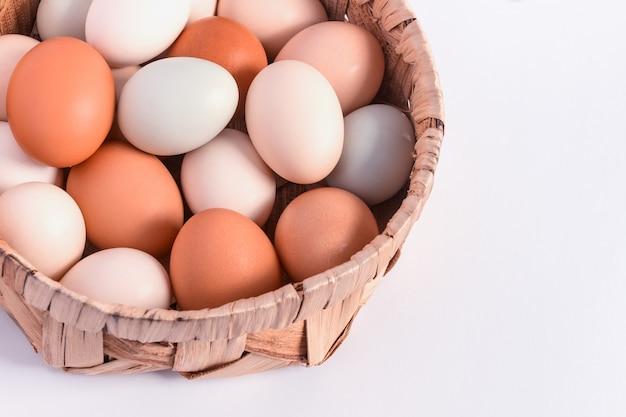 Kolorowi pastelowi jajka w łozinowym koszu na bielu