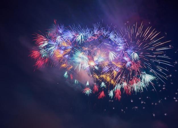 Kolorowi piękni fajerwerki salutują przeciw ciemnemu nocnemu niebu