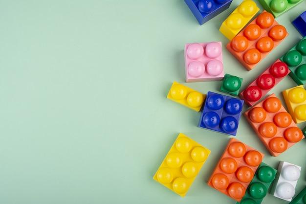 Kolorowi plastikowi budowa bloki na zielonym tle. skopiuj miejsce na tekst.