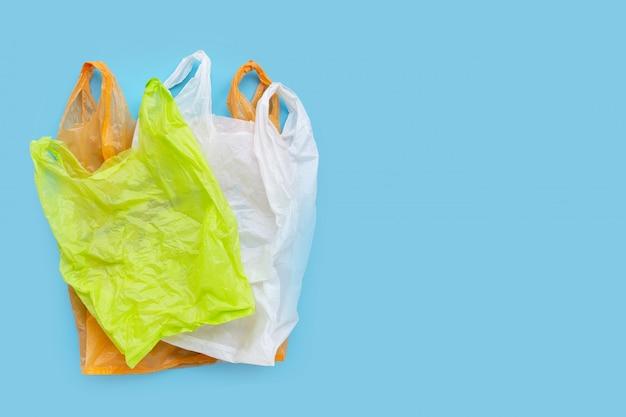 Kolorowi plastikowi worki na błękitnym tle.