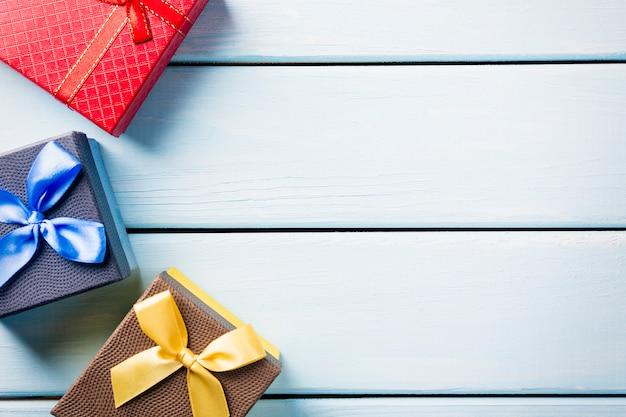 Kolorowi prezentów pudełka na ładnym błękitnym drewnianym tle