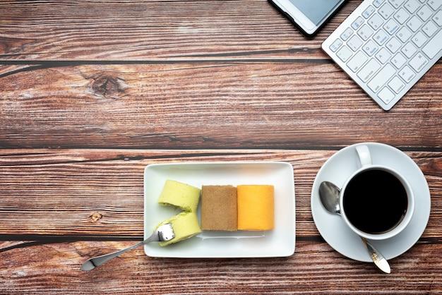 Kolorowi rolka torty, kawa na deseniowym drewnianym tle i