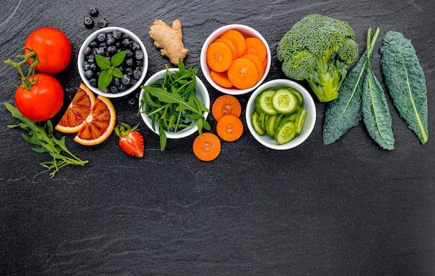 Kolorowi składniki dla zdrowych smoothies i soków na zmroku drylują tło z kopii przestrzenią.