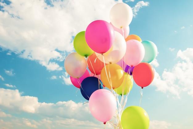 Kolorowi świąteczni balony nad niebieskim niebem